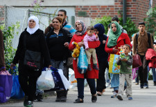 Migrants and refugees arrive at  a tent village at the Donnersberg bridge close to the central train station in Munich, Germany, Sunday Sept. 13,  2015 .Hundreds of thousands of Syrian refugees and others are still making their way slowly across Europe, seeking shelter where they can, taking a bus or a train where one is available, walking where it isn't.  (Andreas Gebert/dpa via AP)